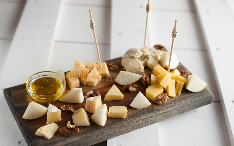 Assorted variety of cheese with honey and nuts. Placed on a dark wooden board. Assortment of different types of cheese with natural honey and walnuts. Placed on stock images