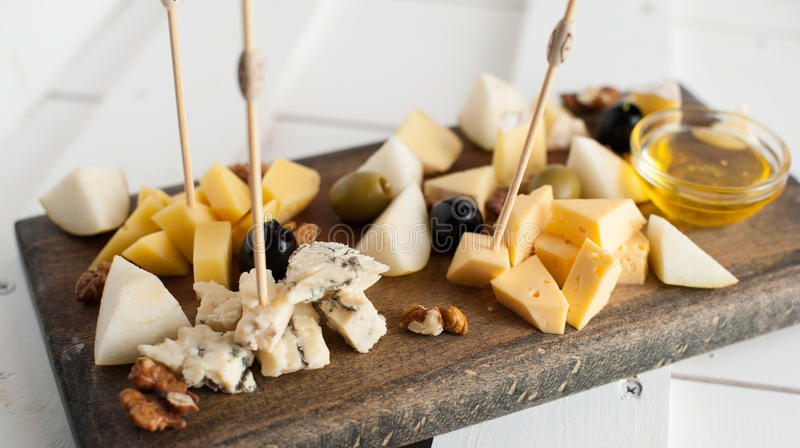 Assorted variety of cheese with honey and nuts. Placed on a dark wooden board. Assortment of different types of cheese with natural honey and walnuts. Placed on royalty free stock photo