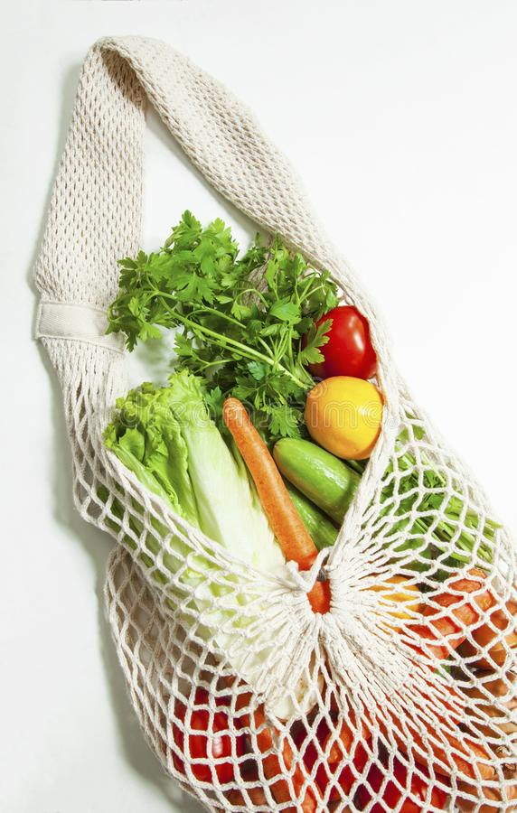 Assorted vegetables in mesh grocery bag isolated on white background royalty free stock images