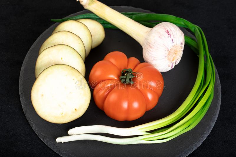 Assorted vegetables. Ob black wooden plate stock photos