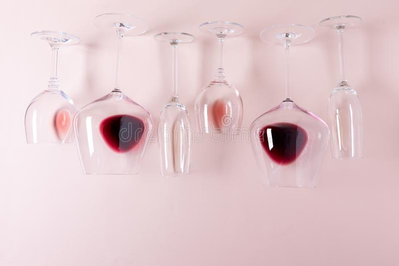 Assorted wineglasses with red, rose and white wine lying top edge on pink background. Wine degustation concept. Flat lay. Top view. Copy space royalty free stock images