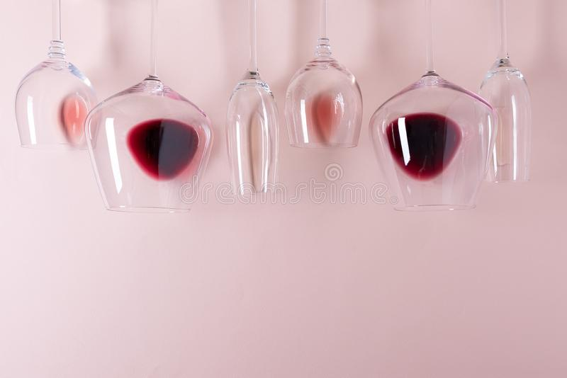 Assorted wineglasses with red, rose and white wine lying top edge on pink background. Wine degustation concept. Flat lay. Top view. Copy space royalty free stock image