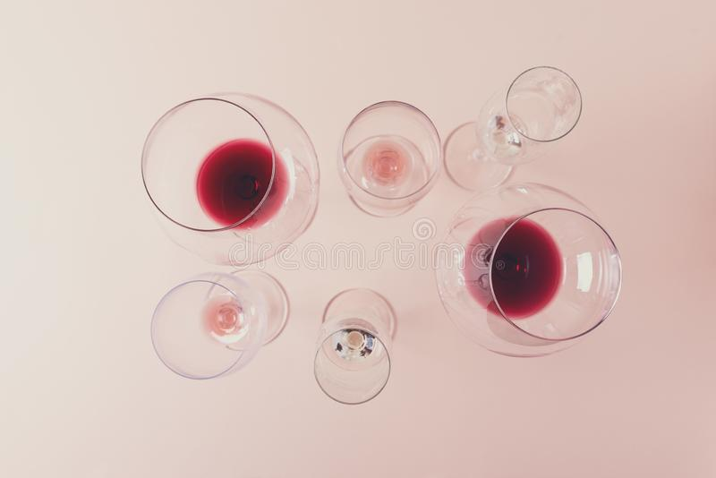 Assorted wineglasses with red, rose and white wine stay on pink background. Wine degustation concept. Flat lay. Top view. Copy. Space. Toned royalty free stock photo