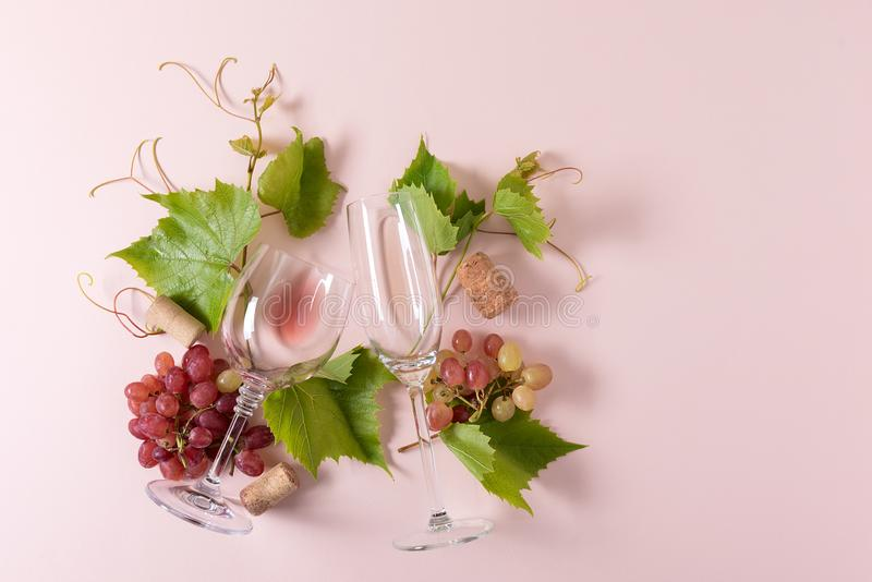 Assorted wineglasses with rose and white wine, grape, leaves and cork lying on pink background. Wine degustation concept. Flat lay. Top view. Copy space royalty free stock images