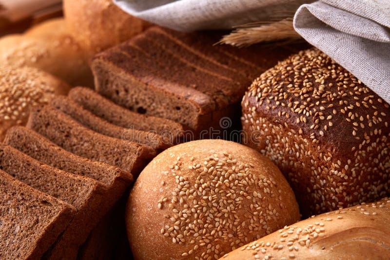 Assortement des frisch gebackenen traditionellen Brotes mit den Ohren des Weizens und des weißen Stoffes stockfotografie