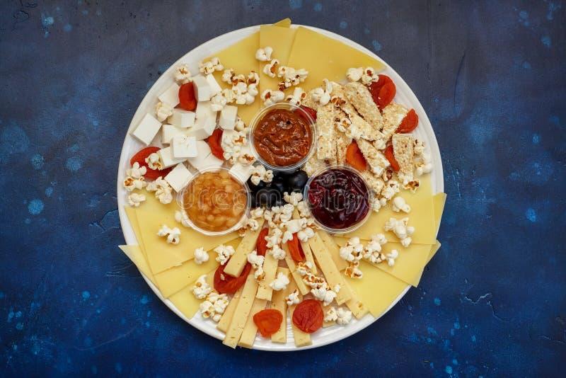Assorti del formaggio con le salse ed il popcorn fotografia stock
