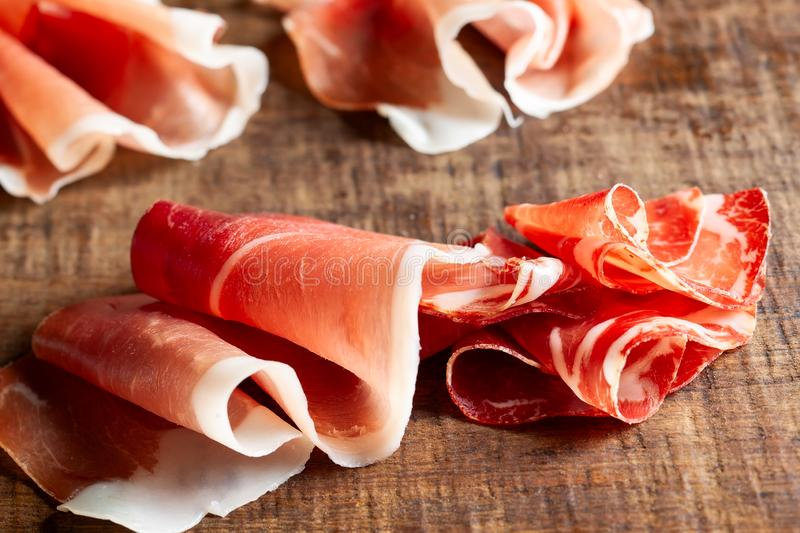 Assorti of sliced jamon, salami, ham  on wooden background stock photo