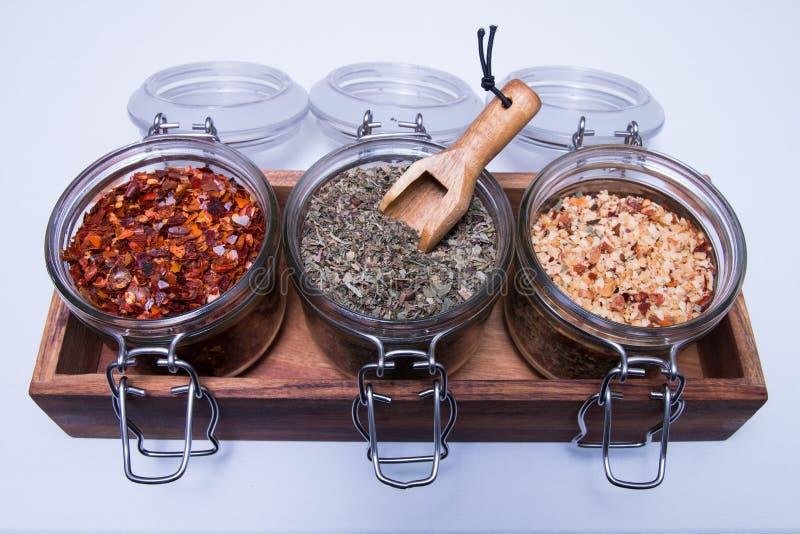 Assortiment de différentes épices dans le pot en verre d'isolement sur le blanc image stock
