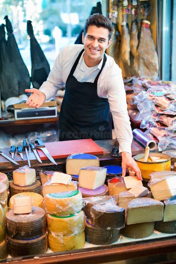 Assortiment de offre de sourire de vendeur masculin de fromage photo stock