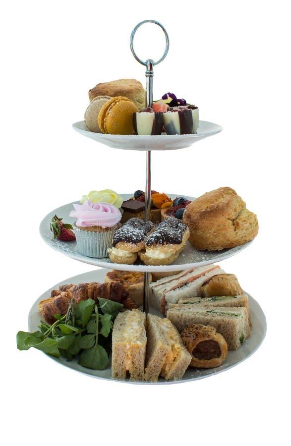 Assortiment des délicatesses de goûter comprenant des sandwichs, scones, tartes, desserts doux d'isolement images libres de droits