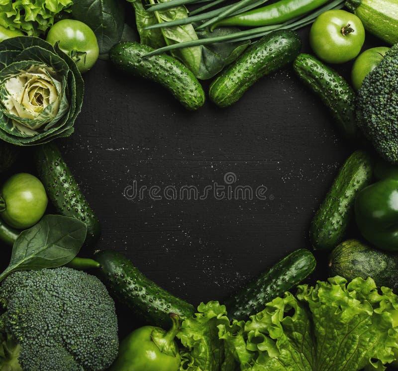 Assortiment des légumes verts frais dans la forme de coeur sur le fond noir image libre de droits