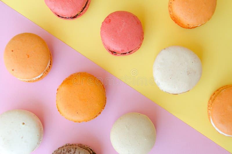 Assortiment des macarons sur le jaune - le fond rose s'est divisé diagonalement en deux triangles photographie stock