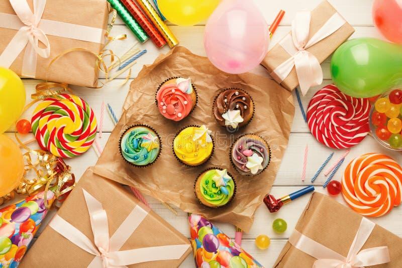 Assortiment des petits gâteaux savoureux et un bon nombre de décorations de fête d'anniversaire images stock