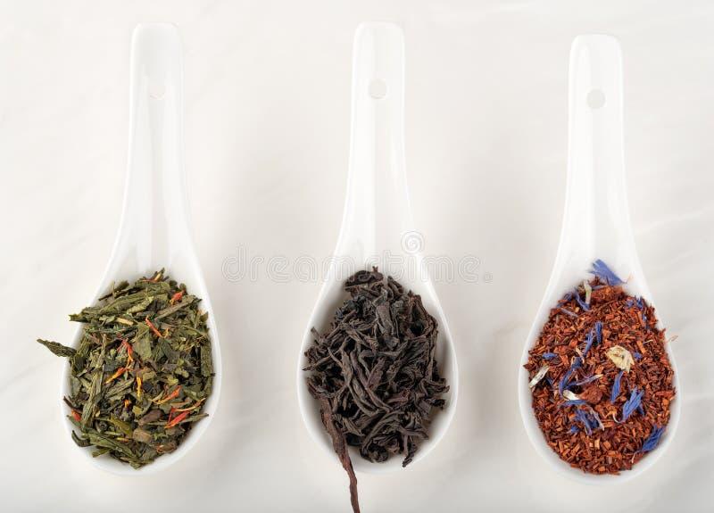 Assortiment des rooibos secs de thé, noir, vert, en PS en céramique blanc photos libres de droits