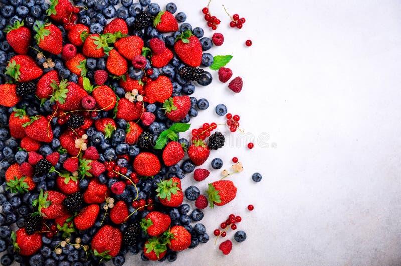 Assortiment van aardbei, bosbes, bes, muntbladeren De achtergrond van de zomerbessen met exemplaarruimte voor uw tekst bovenkant royalty-vrije stock afbeeldingen