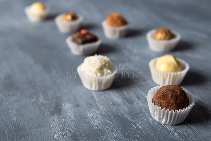 Assortiment van fijn chocoladesuikergoed, wit, dark en melkchocola op grijze achtergrond De snoepjesachtergrond, zijaanzicht, slu royalty-vrije stock afbeelding