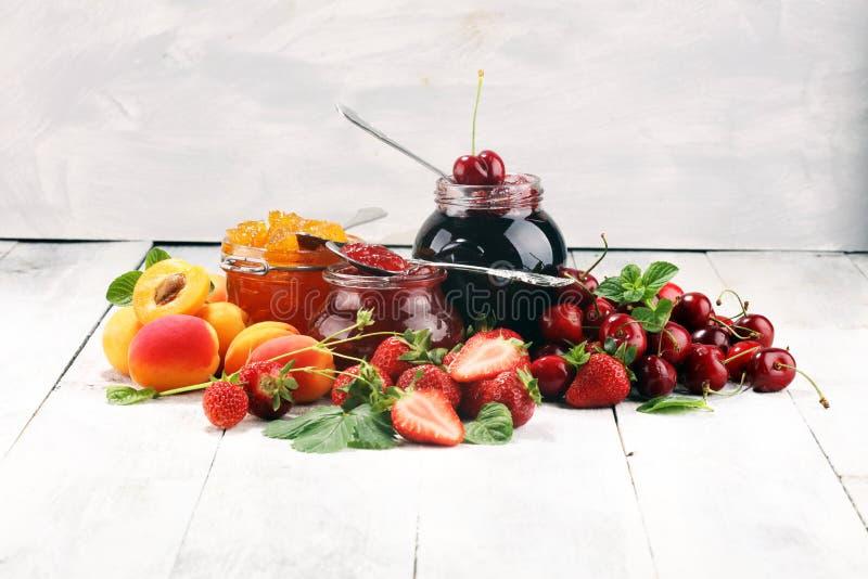 Assortiment van jam, seizoengebonden bessen, abrikoos, munt en vruchten marmelade of confiture stock foto's