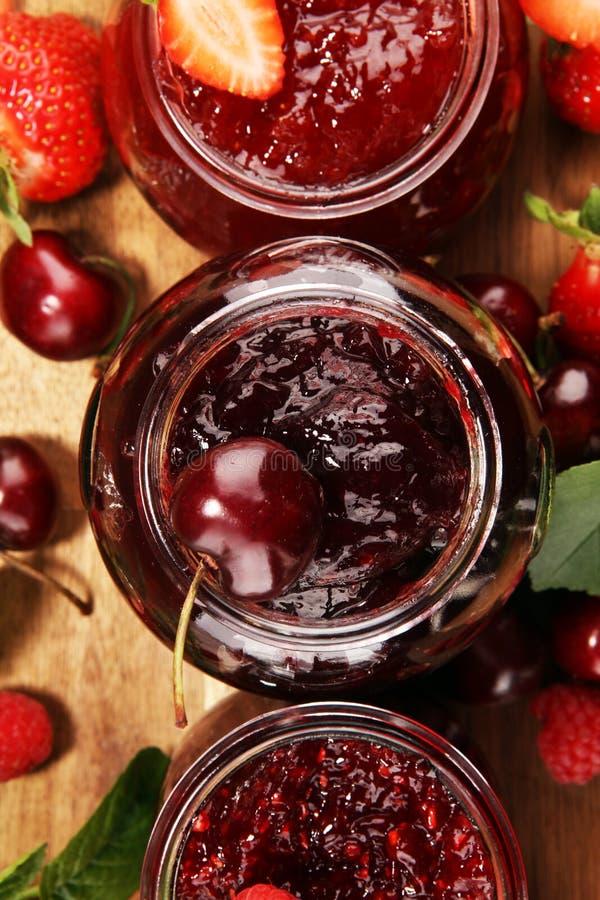 Assortiment van jam, seizoengebonden bessen, kers, munt en vruchten in glaskruik stock fotografie