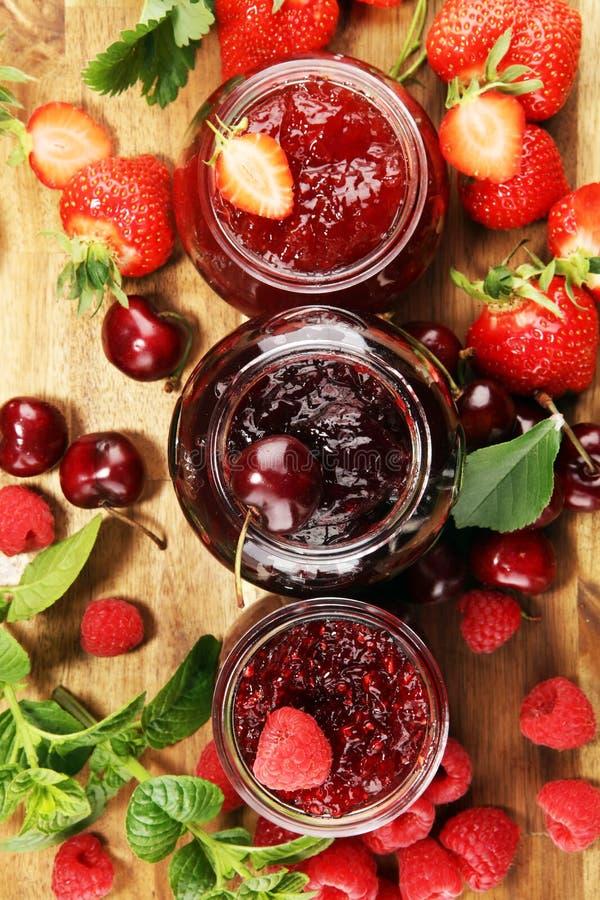 Assortiment van jam, seizoengebonden bessen, kers, munt en vruchten in glaskruik royalty-vrije stock foto