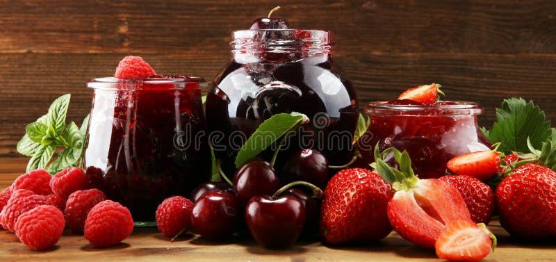 Assortiment van jam, seizoengebonden bessen, kers, munt en vruchten in glaskruik stock afbeelding