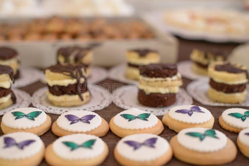 Assortiment van kleine, vlakke, knoop-als koekjes, overladen met kleurrijke het berijpen vlinders, bij suikergoed en cakebar, bij royalty-vrije stock fotografie