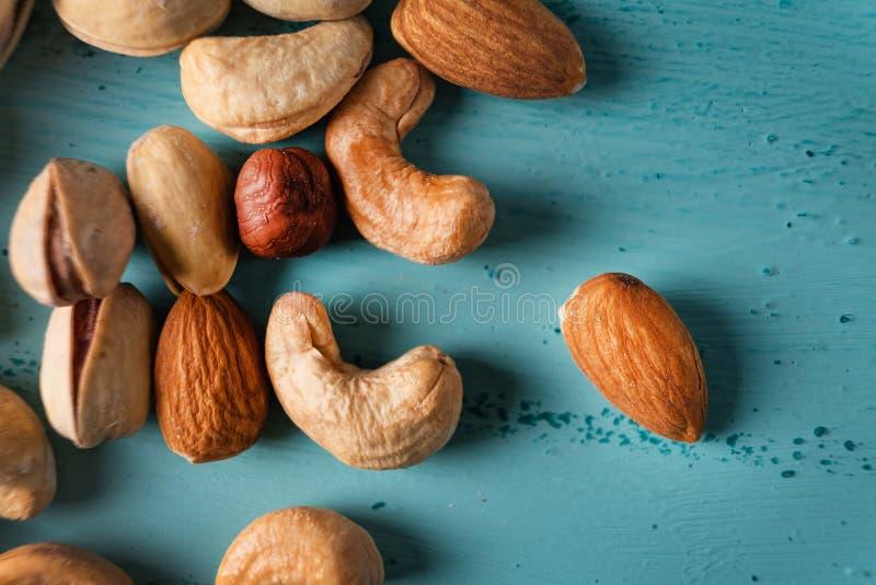 Assortiment van noten in houten kom op blauwe houten lijst Cachou, hazelnoten, amandelen royalty-vrije stock foto's
