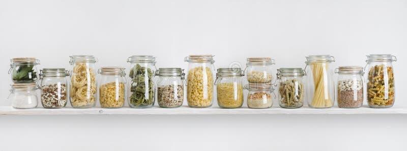 Assortiment van ongekookte die kruidenierswinkels in glaskruiken op plank worden geschikt stock afbeelding