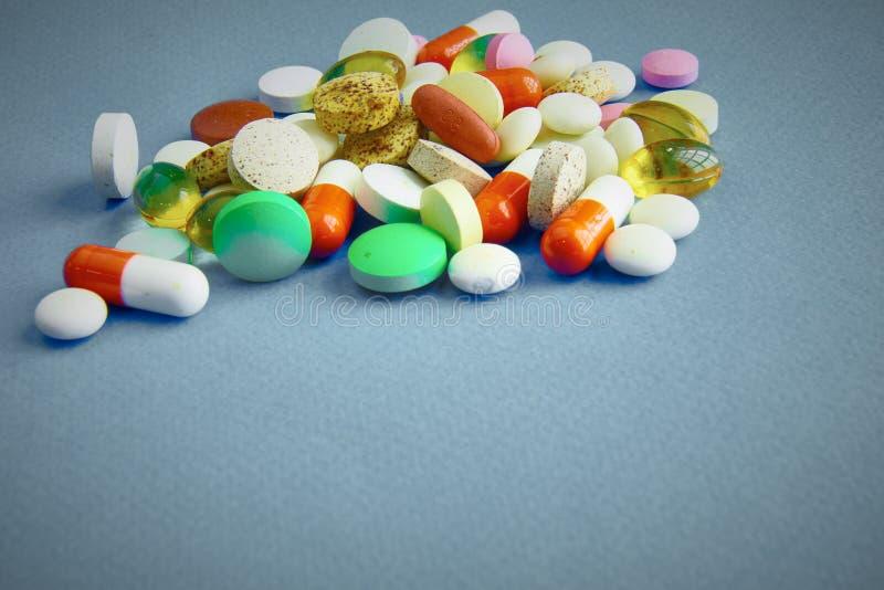 Assortiment van pillen, tabletten en capsules op lijst stock afbeeldingen