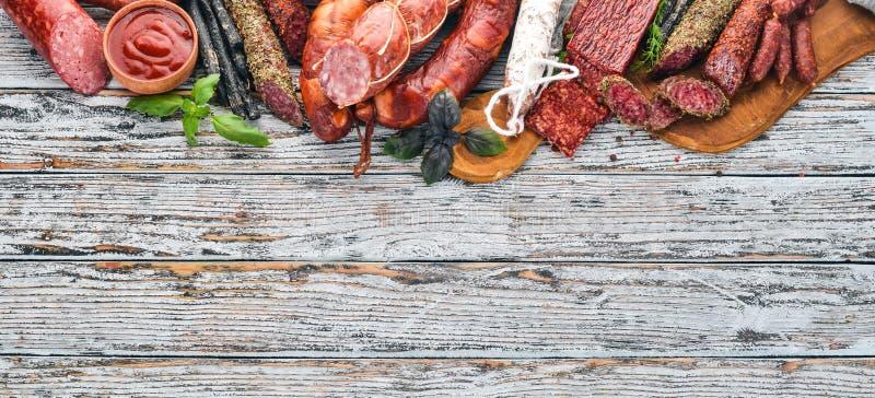 Assortiment van salami en snacks Worst Fouet, worsten, salami, paperoni Op een witte houten achtergrond royalty-vrije stock foto's