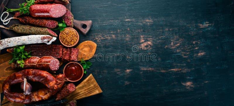 Assortiment van salami en snacks Worst Fouet, worsten, salami, paperoni Op een zwarte houten achtergrond stock foto's