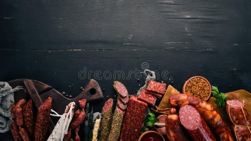 Assortiment van salami en snacks Worst Fouet, worsten, salami, paperoni Op een zwarte houten achtergrond stock foto