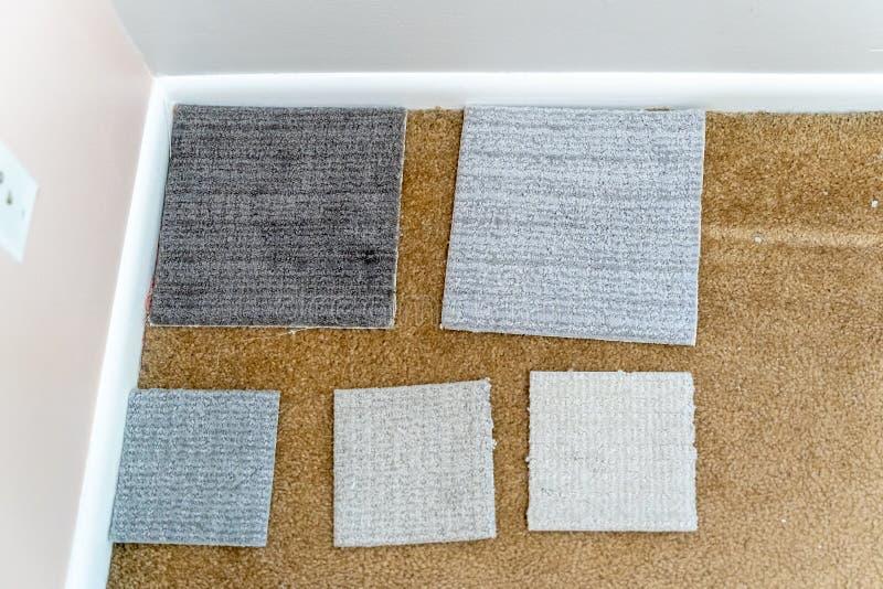 Assortiment van tapijtsteekproeven over oud, vuil tapijt in een huis, klaar om over nieuwe bevloering te beslissen die worden opg stock foto's