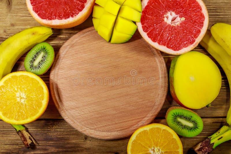 Assortiment van tropische vruchten op houten lijst Stilleven met bananen, mango, sinaasappelen, grapefruit en kiwivruchten royalty-vrije stock foto