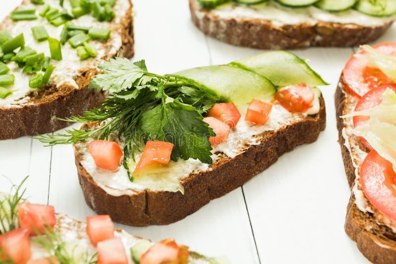 Assortiment van vegetarische sandwiches met groenten en kaas op een witte lijst Selectieve nadruk stock afbeeldingen