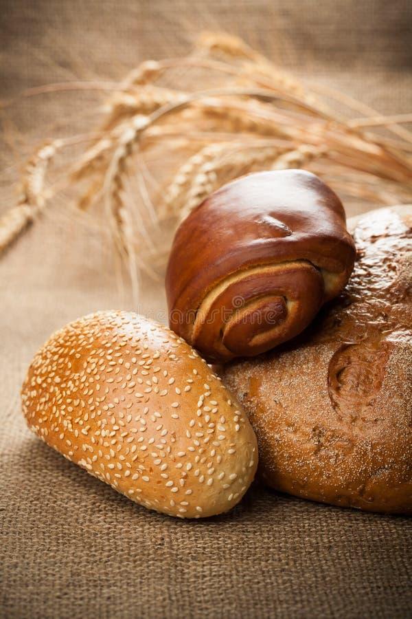 Assortiment van vers gebakken brood op de jute stock foto's