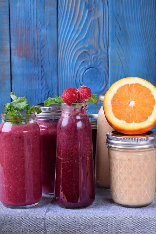 Assortiment van verschillende die smoothies met vruchten, bessen en munt op de lijst wordt bedekt stock foto