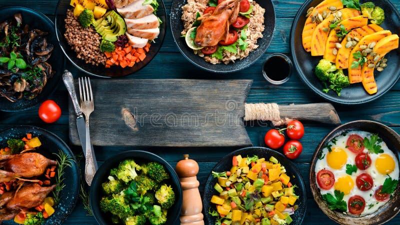 Assortiment van voedsel Salade, avocado, kwartels, paddestoelen, pompoen Op een blauwe houten achtergrond royalty-vrije stock foto