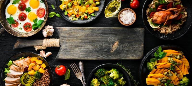 Assortiment van voedsel Salade, avocado, kwartels, paddestoelen, pompoen Op een zwarte achtergrond stock afbeelding