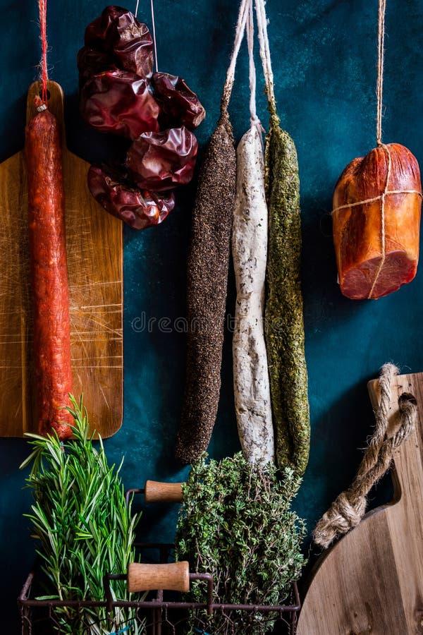 Assortiment van worsten, Spaanse charcuterie, houten scherpe raad, verse tuinkruiden stock foto