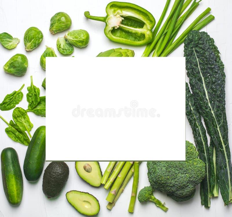 Assortiment vert de légumes et d'herbes sur un fond blanc images stock