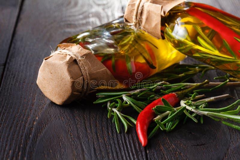 Assortimento degli oli piccanti con le erbe e le spezie in bottiglie differenti immagini stock