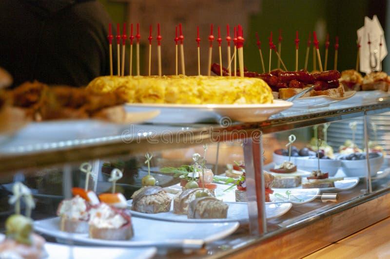 Assortimento degli spiedi e dei tapas nell'esposizione del ristorante Omelette delle patate, montaditos fotografia stock libera da diritti