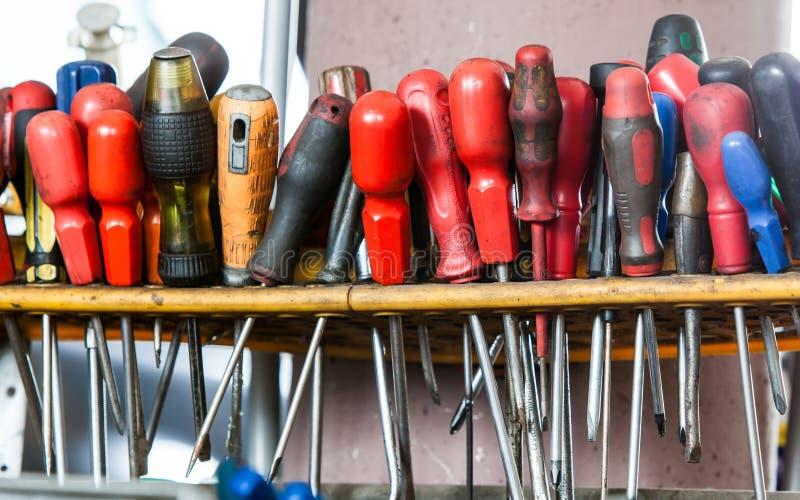 Assortimento degli strumenti che appendono sulla parete. Cacciaviti nel servizio dell'automobile del garage del meccanico immagine stock libera da diritti