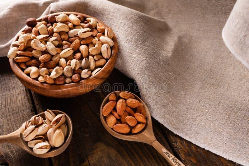 Assortimento dei dadi in ciotola di legno sulla tavola di legno scura Anacardio, nocciole, mandorle e pistacchi fotografia stock