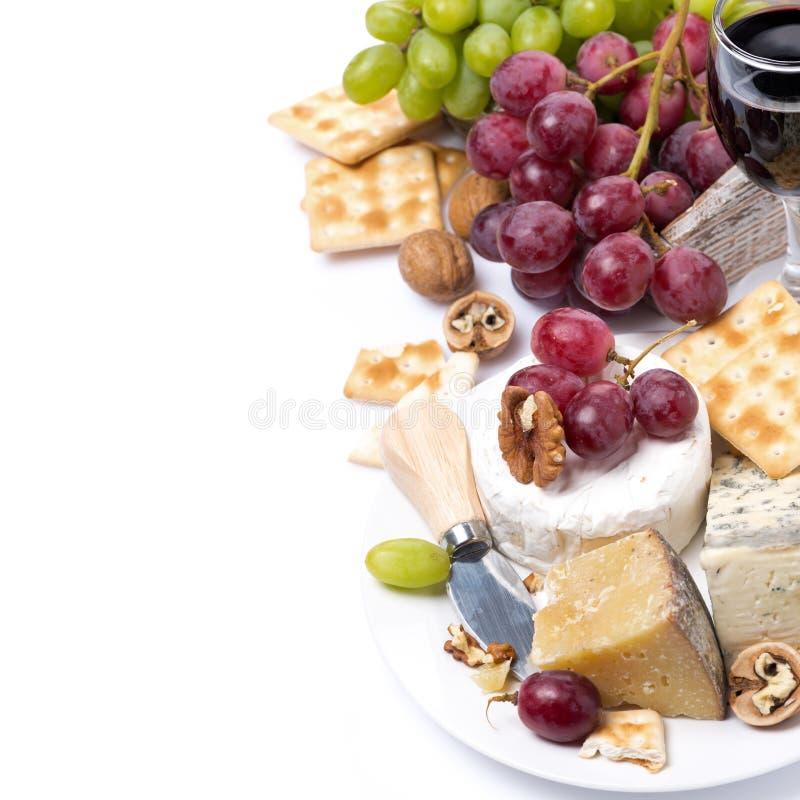 Assortimento dei formaggi, vetro di vino rosso, uva, cracker immagini stock
