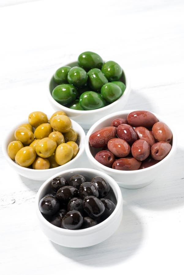 assortimento dei generi differenti di olive organiche sulla tavola bianca fotografia stock libera da diritti
