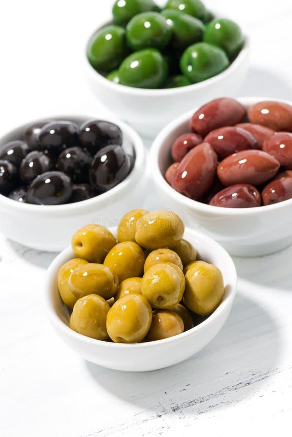 Assortimento dei generi differenti di olive organiche sulla tavola bianca, vista superiore verticale immagine stock