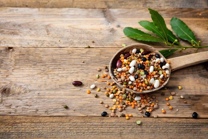 Assortimento dei legumi in una siviera e rovesciati su un fondo da tavolo di legno, spazio della copia fotografie stock libere da diritti