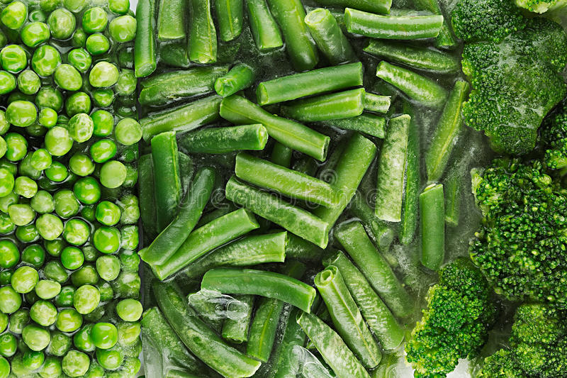 Assortimento dei piselli congelati freschi, fagiolino, broccoli con il primo piano di brina come fondo fotografia stock libera da diritti