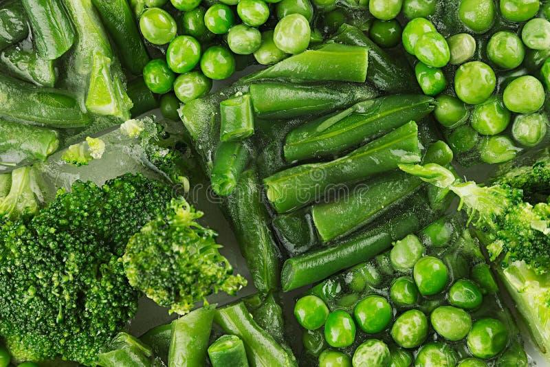 Assortimento dei piselli congelati freschi, fagiolino, broccoli con il primo piano di brina come fondo fotografie stock libere da diritti